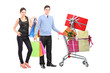 Couple holding bags and posing next to a shopping cart