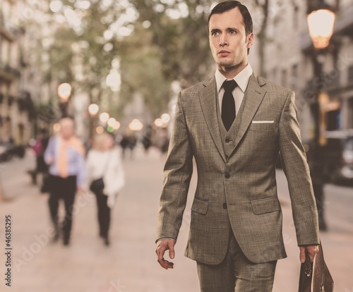 Man in classic grey suit with briefcase walking outdoors - 46385295
