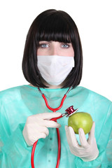 Female surgeon holding a green apple
