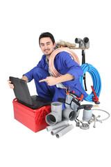 plumber kneeling showing computer