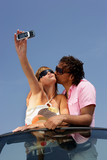 Funky couple in a convertible taking a photo on a cellphone