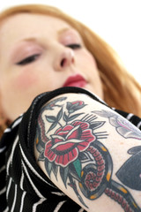 Red Head Looking at Her Forearm Covered in Tattoos
