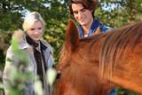 Couple stood by beautiful horse