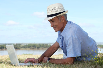 Man with computer at edge of river