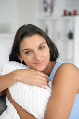 Woman hugging a cushion