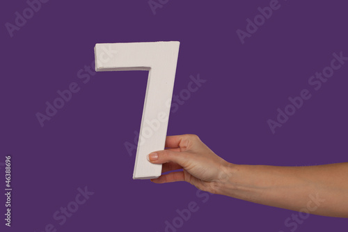 Female hand holding up the number 7 from the right