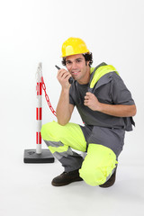 Worker in reflective work-wear using radio receiver