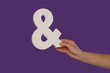 Female hand holding up an ampersand from the right