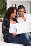 couple with laptop in lounge