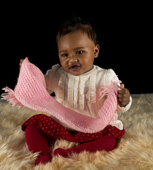 Black baby girl playing with a pink scarf