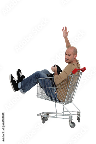 Bald man sat in trolley with steering wheel