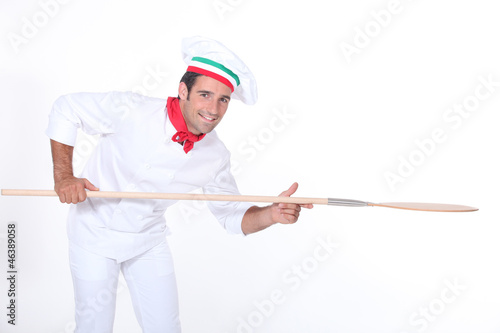 Pizza maker holding a pizza peel