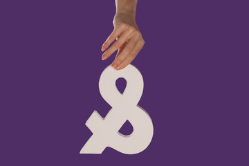 Female hand holding up an ampersand from the top