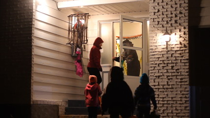 Children with family in Halloween costumes trick or treating