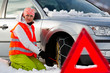 Winter road, woman putting snow chains onto tyre of car