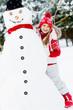 Winter fun, happy girl making a snowman