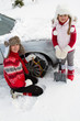 Winter road, family putting snow chains onto tyre of car
