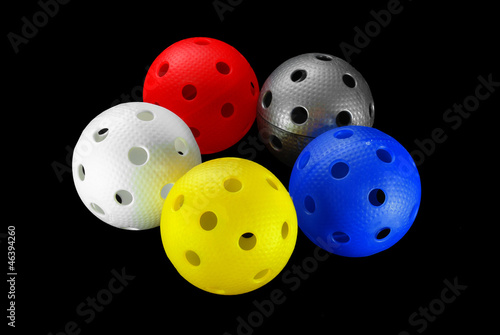Five floorball balls isolated on a black background