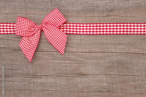 Eine rotkarierte Schleife auf Holz