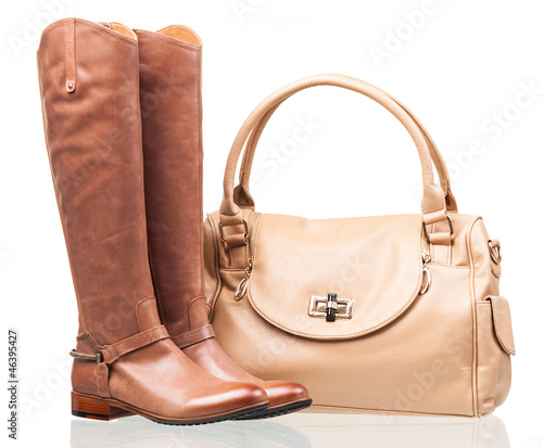 Women knee-high boots and leather bag over white