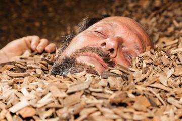alter Mann schläft in Hackschnitzel