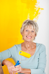 ältere dame streicht ihre wohnung gelb