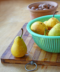 Yellow pears and walnuts on a table