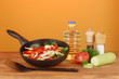 frying pan with vegetables on red background