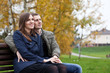 young couple sitting on bench in autumn park