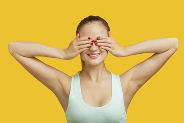 Beautiful young woman covering eyes over yellow background