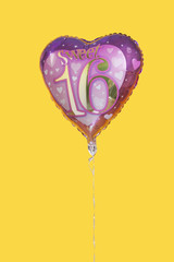 Heart shaped birthday balloon over yellow background