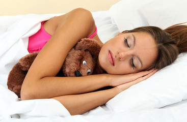 young beautiful woman sleeping with fluffy bear in bed