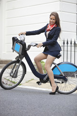 Portrait of young businesswoman standing with bicycle