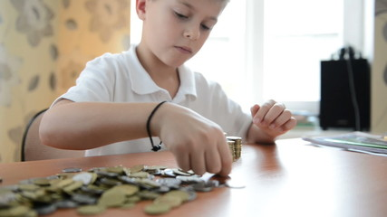 Child builds construction from coins. Dolly shot. Full HD