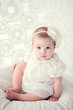 cute baby girl in white fashion dress with flower on her hair