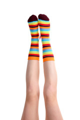 female legs in colorful striped socks isolated on white