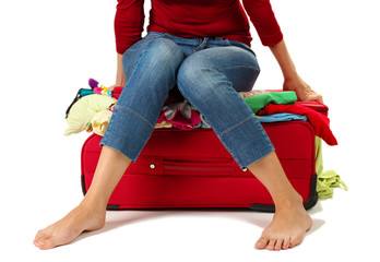 The girl is trying to close suitcase crammed on white