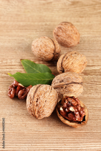 walnuts with green leaves, on wooden background