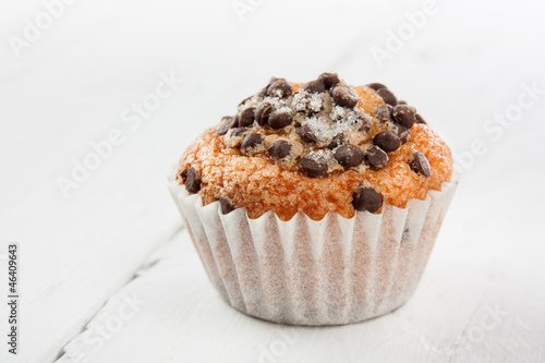 Chocolate chip muffin on white wood