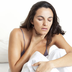 woman with sore throat sitting in bad