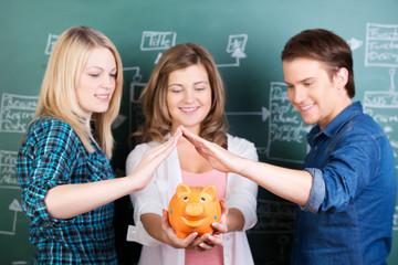 drei studenten mit sparschwein