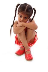 enfant triste assise sur fond blanc