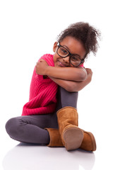 Cute young African American girl seated on the floor