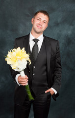 groom with a bouquet in studio