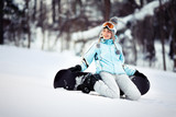 Young female snowboarder sitting on the snow