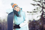 Young woman with snowboard in sunlight
