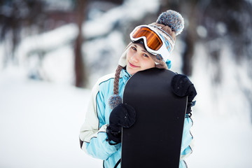 Smiling girl holding her snowboard