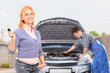 Careless female holding a key while mechanic is checking her car
