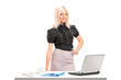 Professional woman standing next to office desk with laptop