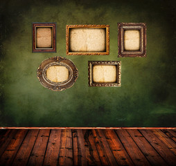 Retro room with empty antique frames on grunge green wall